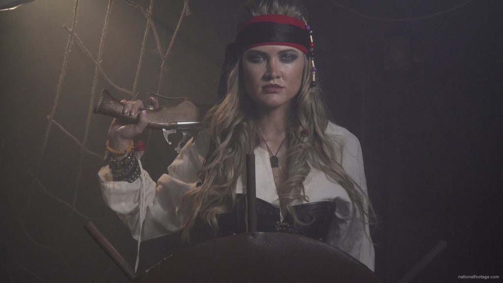 Captain-pirate-woman-stands-near-the-ship-helm-and-floats-against-wind_001 🔴  National Footage