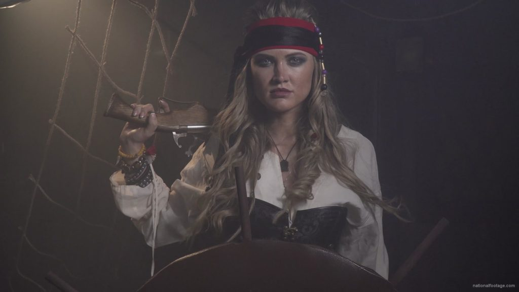 Captain-pirate-woman-stands-near-the-ship-helm-and-floats-against-wind_004 🔴  National Footage