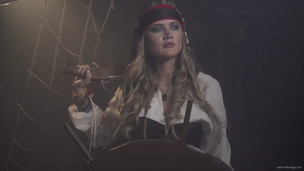 Captain-pirate-woman-stands-near-the-ship-helm-and-floats-against-wind_005 🔴  National Footage