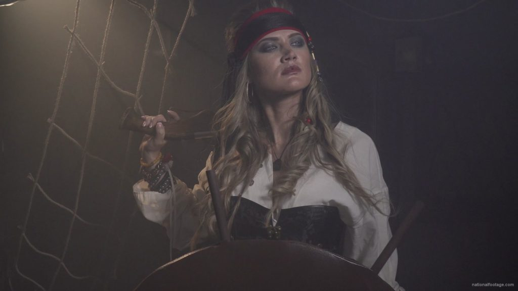 Captain-pirate-woman-stands-near-the-ship-helm-and-floats-against-wind_006 🔴  National Footage