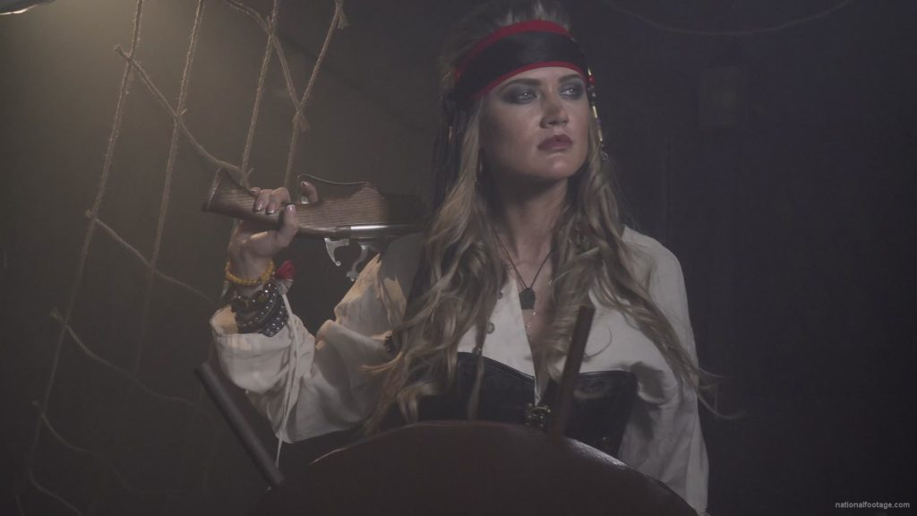 Captain-pirate-woman-stands-near-the-ship-helm-and-floats-against-wind_009 🔴  National Footage