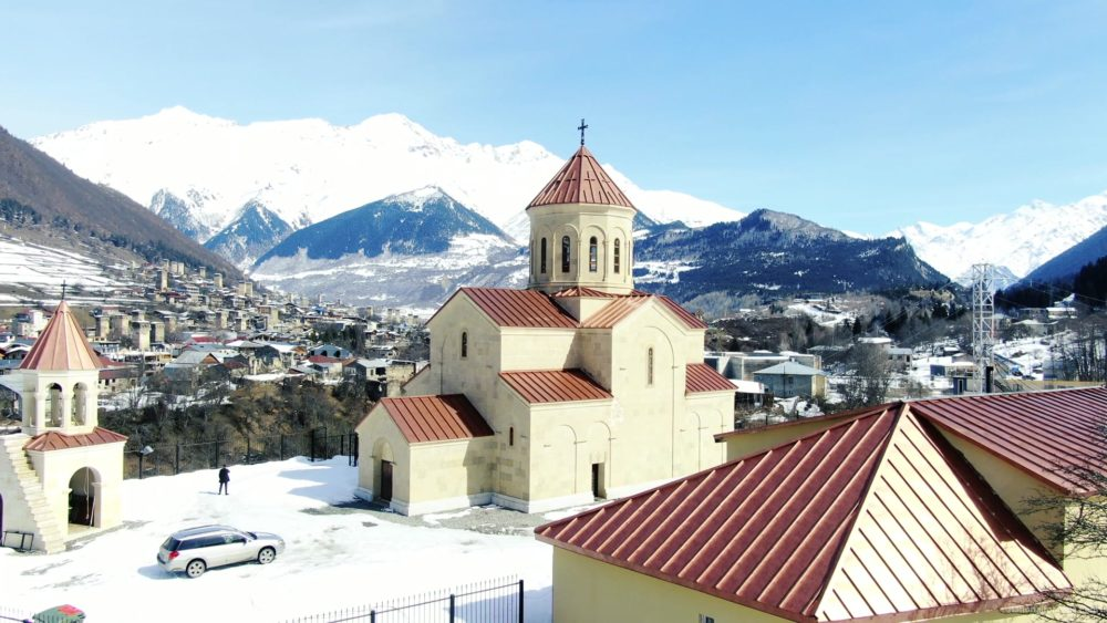 vj video background Beautiful-church-on-the-background-of-the-great-snow-capped-mountains-from-the-height-of-the-birds-eye_003