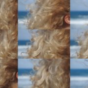 Bright-blonde-hair-play-with-wind-in-slow-motion-on-sea-background National Footage