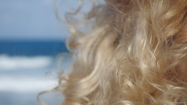 Bright-blonde-hair-play-with-wind-in-slow-motion-on-sea-background_004 National Footage