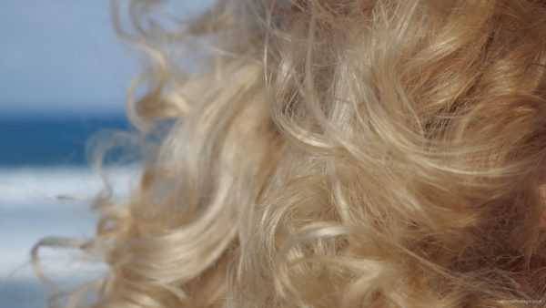 Bright-blonde-hair-play-with-wind-in-slow-motion-on-sea-background_005 National Footage