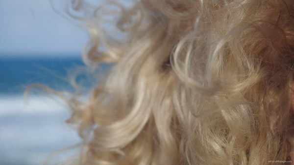 Bright-blonde-hair-play-with-wind-in-slow-motion-on-sea-background_008 National Footage