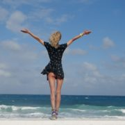 Girl-travel-raises-her-arms-and-hands-up-in-slow-motion-on-the-sea-ocean-beach_004 National Footage