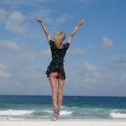 Girl-travel-raises-her-arms-and-hands-up-in-slow-motion-on-the-sea-ocean-beach_007 National Footage