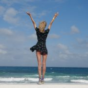 Girl-travel-raises-her-arms-and-hands-up-in-slow-motion-on-the-sea-ocean-beach_008 National Footage
