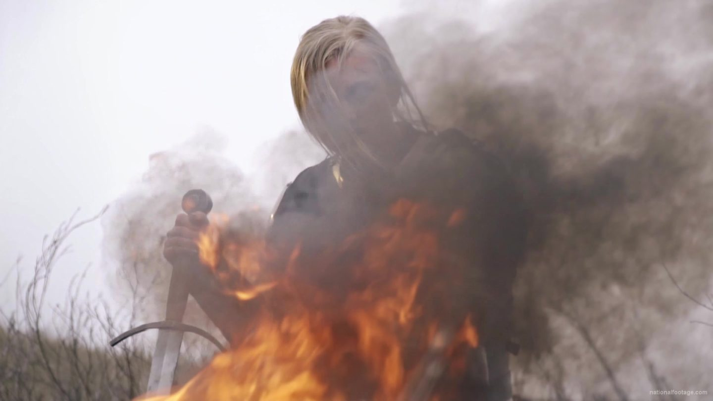 vj video background Sad-blonde-woman-knight-heating-near-fire-with-sword-in-France_003